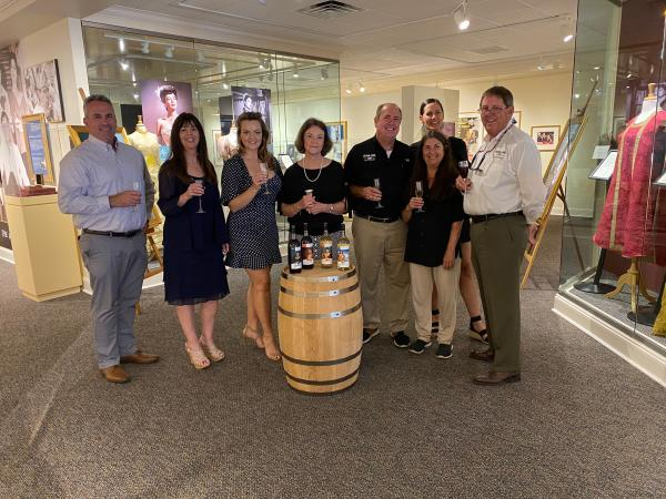 A group gathered inside the Ava Gardner Museum with the Ava Gardner Signature Wine Collection presented on a barrel in front of them.
