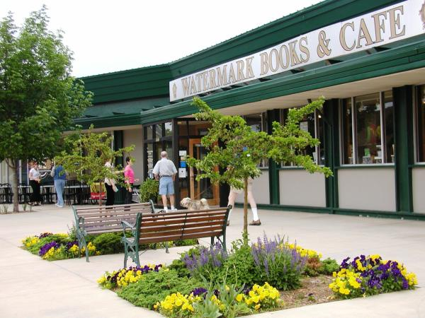 An exterior view of Watermark Books & Cafe in Wichita with two benches in front and blooming yellow and purple flowers