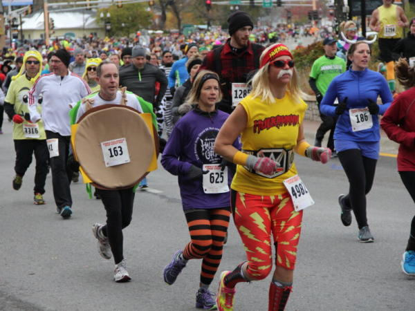 Costumed runners compete in a race during Anoka Halloween