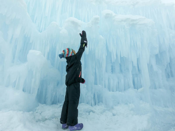 Young boy looking up at an ice wall