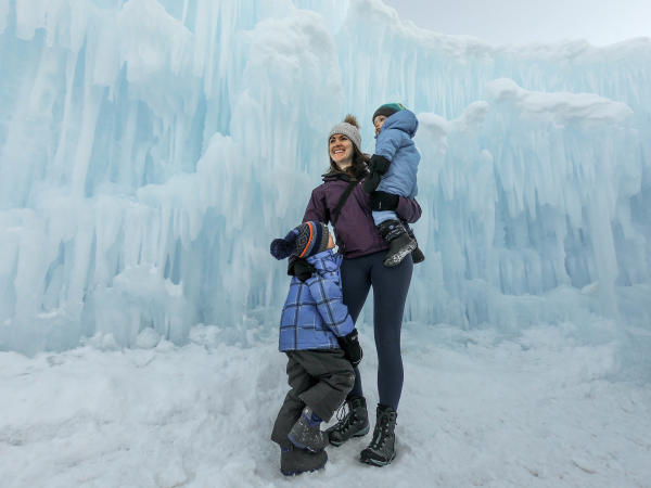 Mother with two children in front of ice castle wall