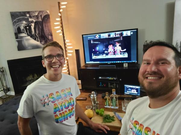 two men watching TV and having cocktails.