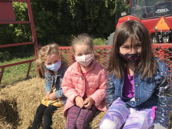 Kids wearing face masks on a Hayride