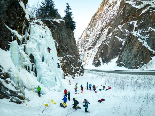 ice climbers ascend a frozen waterfall in a canyon