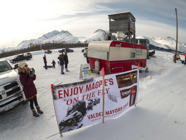 a foodtruck and spectators near a snowmachine race