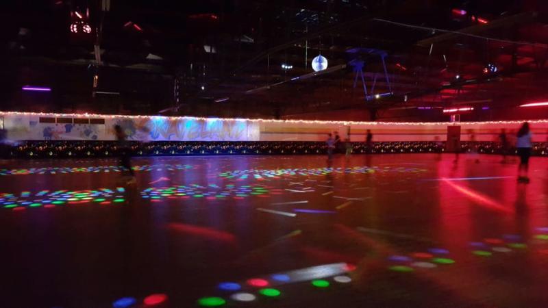 People skating on the disco-lit floor of Western Skateland