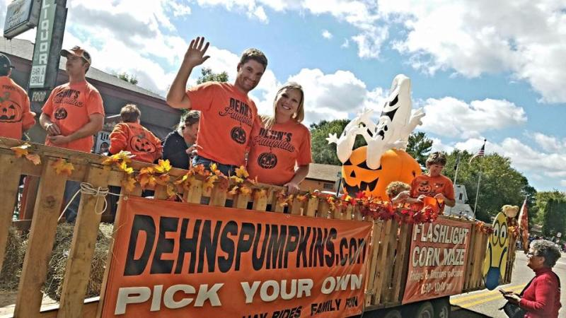 """People on float where orange t-shirts above a matching sign advertising """"Dehn's Pumpkins"""" during a Halloween parade"""