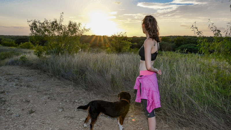 Girl with dog on trails at sunset