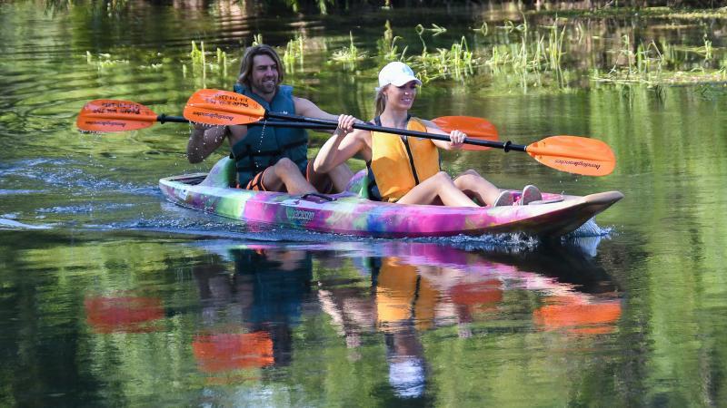 Couple in kayak paddling river