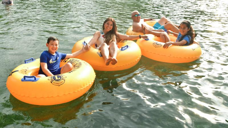 Family with two kids tubing on river
