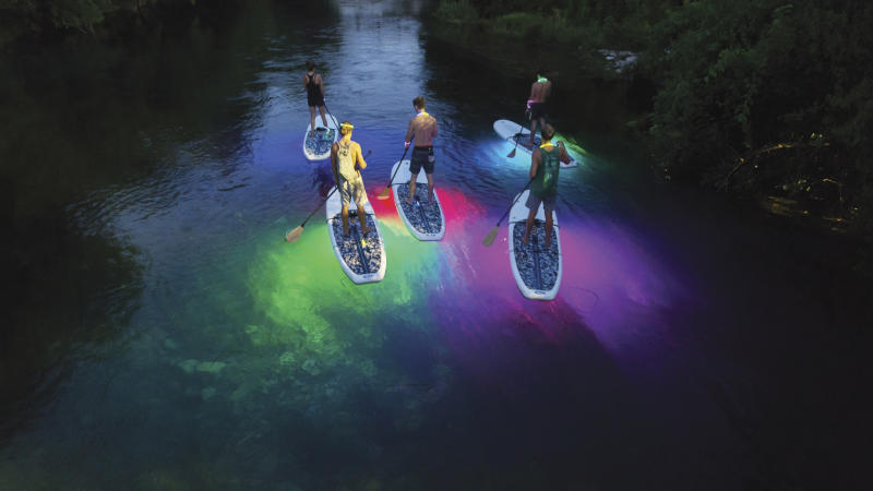 Group on glowing stand-up paddle boards at night