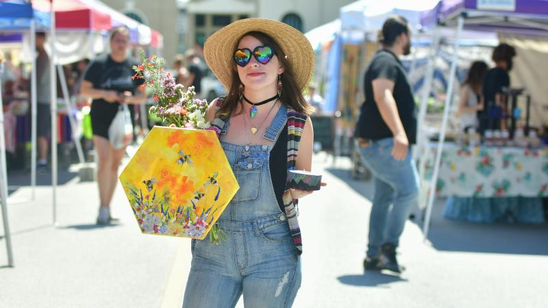 Woman at outdoor market with painting and flowers