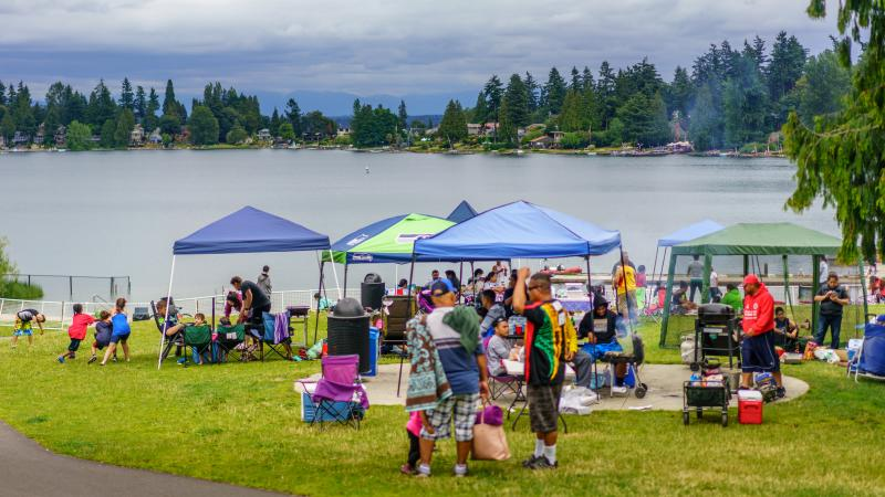 Families celebrating under tents with Angle Lake in the background