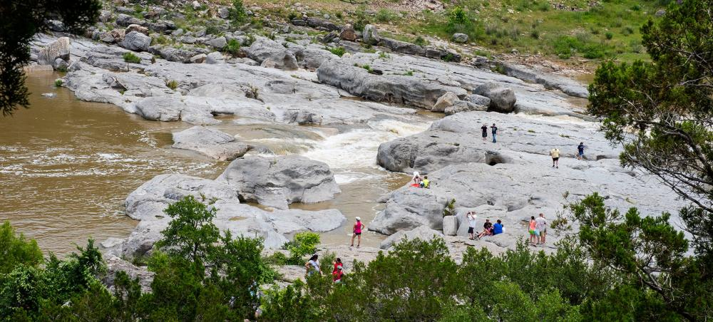 People hiking around rock formations at Pedernales Falls State Park near Austin Texas