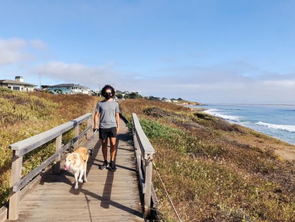 man walking his dog along a boardwalk in Cambria in SLO CAL