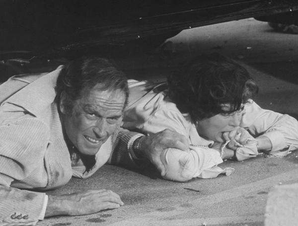 Ava Gardner and her Earthquake co-star lay under a car in this behind the scenes black and white photo.