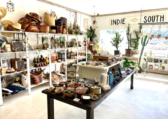 A photo inside Indie South, a gift shop on Hawthorne Ave in Athens, Ga, shows a table covered in books and stones, and white shelves along the left side with wares filling the shelves and baskets stacked on top.