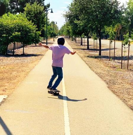 Kid skateboarding along Clovis Trail