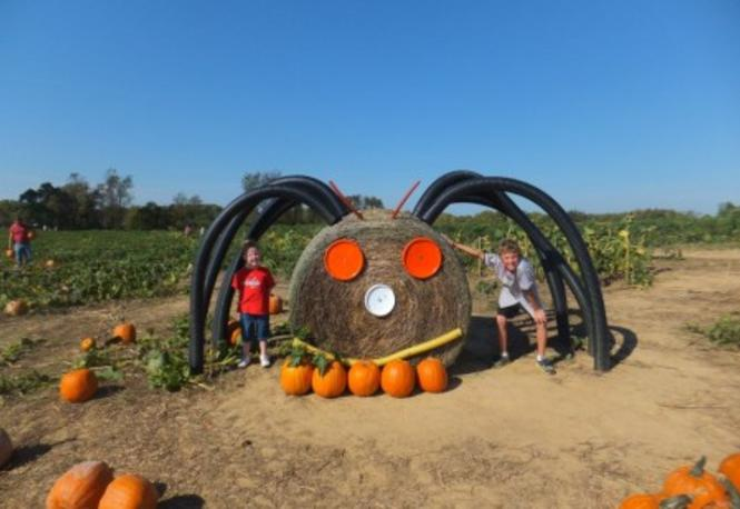 Hay bail spider with two kids standing for a picture