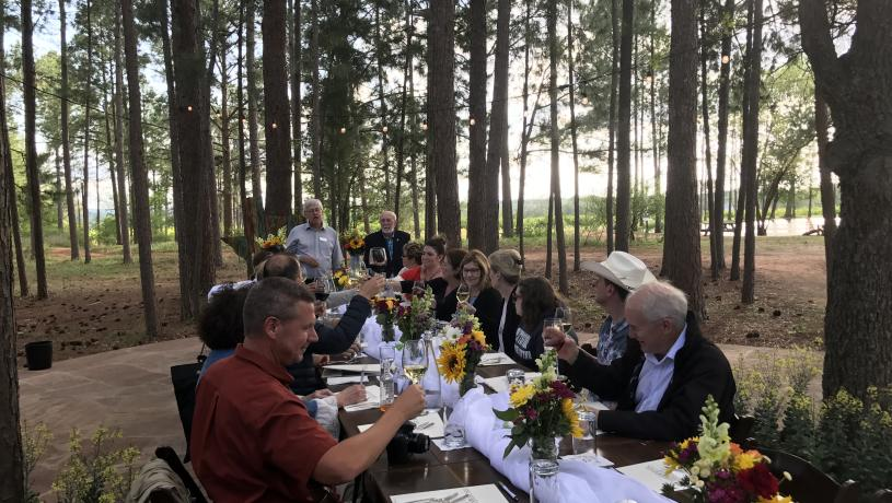 People Eating Together At A Long Table Surrounded By Trees in Fredericksburg, TX