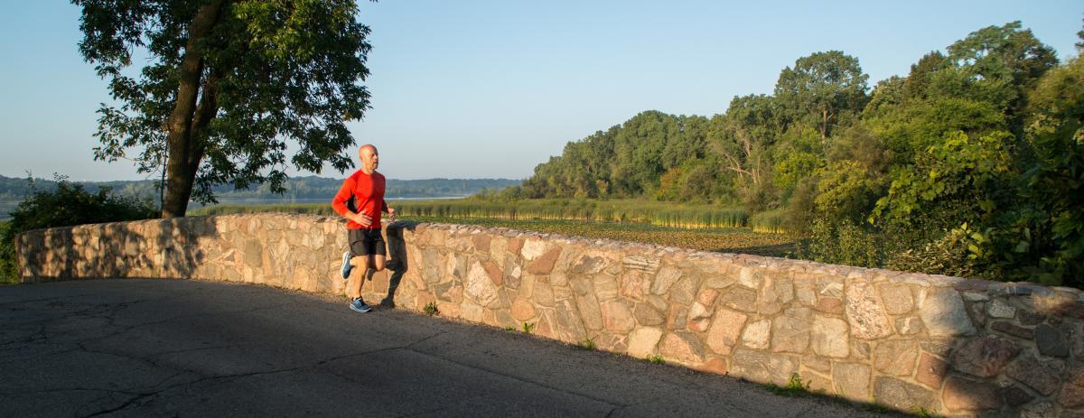 A man runs across a bridge at Lake Wingra in the golden hour.
