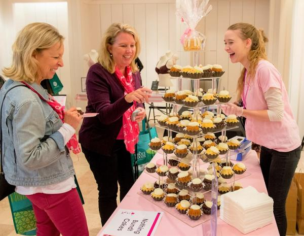 Ladies looking at a tier of cupcakes