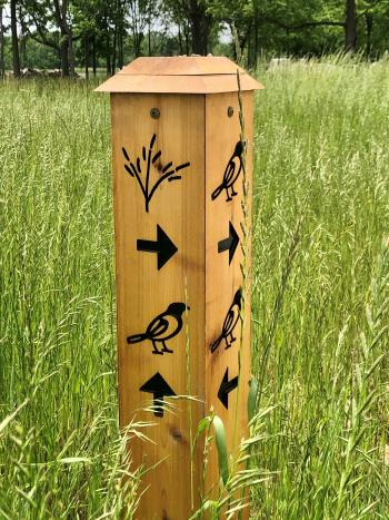 Trail marker at the intersection of Bluestem Bend and Oriole Stroll near the 18-hole disc golf course in W.S. Gibbs Memorial Park.