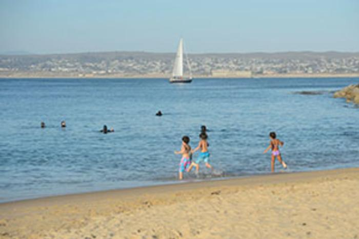 Children run into the ocean with sailboat in the background in Monterey County, CA