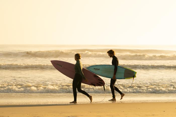 Two surfers explore the shoreline near Nags Head in the Outer Banks.