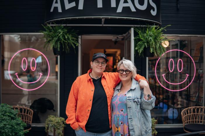 A couple stand close outside their shop.