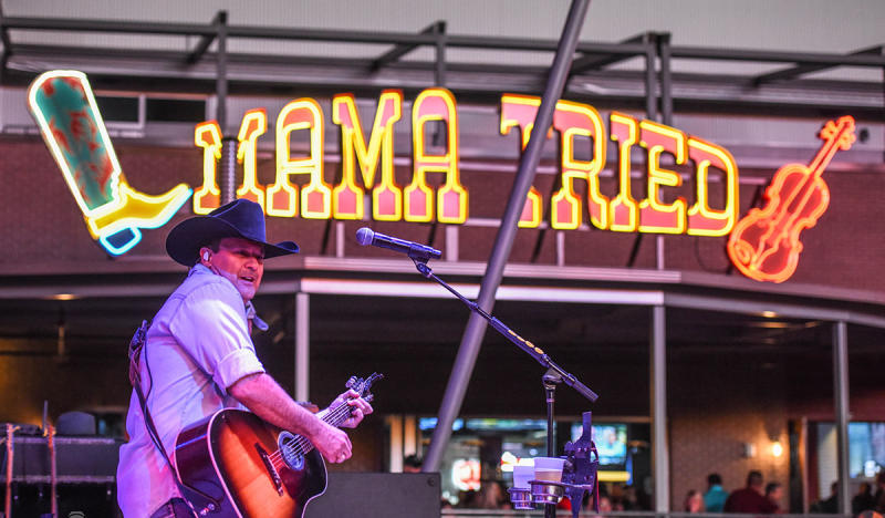 Man with Guitar and cowboys hat on Mama Tried stage