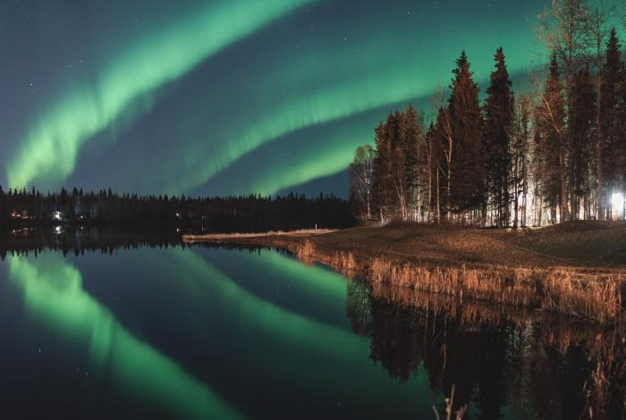 three bands of green aurora in the sky reflecting on a still lake with trees in foreground and background