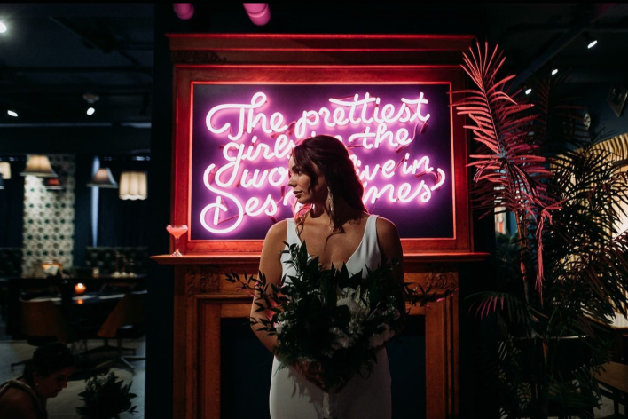 A bride stands in front of a pink neon sign that reads