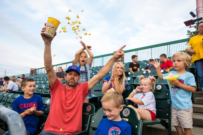 Family cheering and celebrating in the stands at an Iowa Cubs game