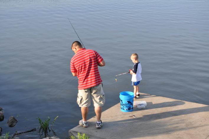Father and Son fishing together off of a dock