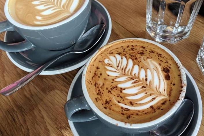 Two cups of coffee with designs from St. Kilda
