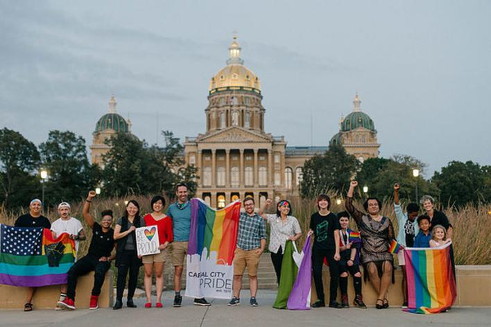 Group of people holding rainbow flags and signs in front of the Iowa State Capitol