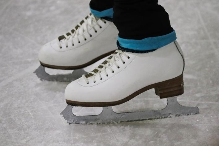 white ice skates with jeans on ice rink