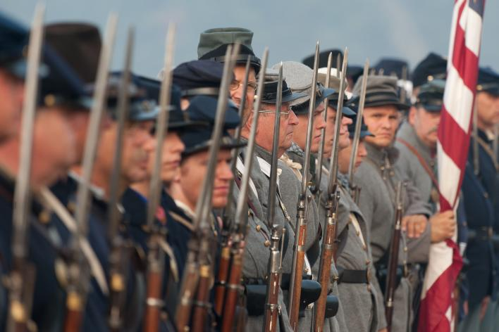 An image of men dressed as soldiers in a civil-war reenactment