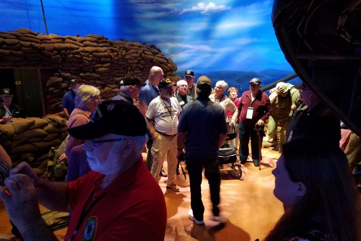 A group of people walking around an exhibit at the National Museum of the Marine Corps for a reunion