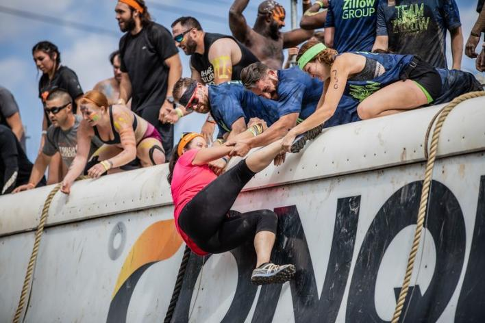 Adventure athletes pulling up female onto climbing wall at a tough mudder race.