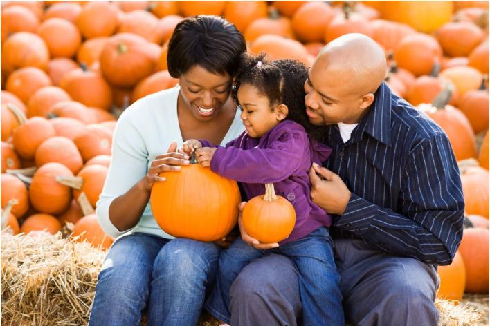 Black family sitting in pumpkin patch with toddler girl