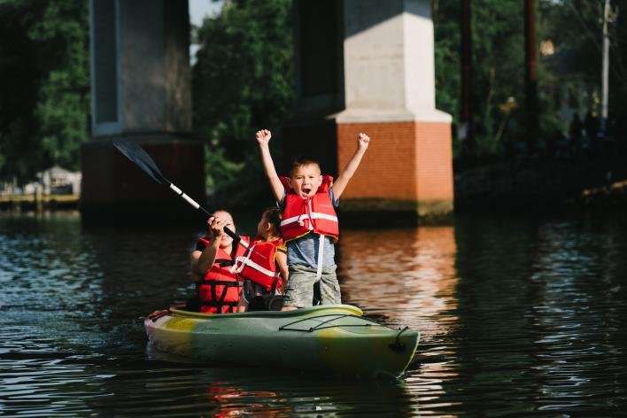 a woman and two children kayaking in a river, one of the children is holding both arms up excited