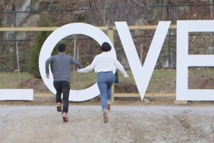 African American couple running towards LOVE sign