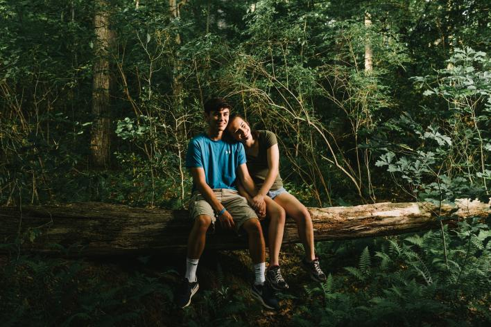 A young man and young woman sitting on a log in the forest