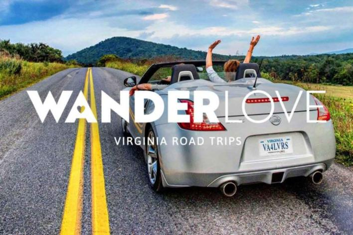couple on a road in a convertible with hands raised in the air WanderLove logo overlayed