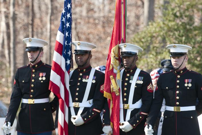 Marines in uniform holding flags for a ceremony