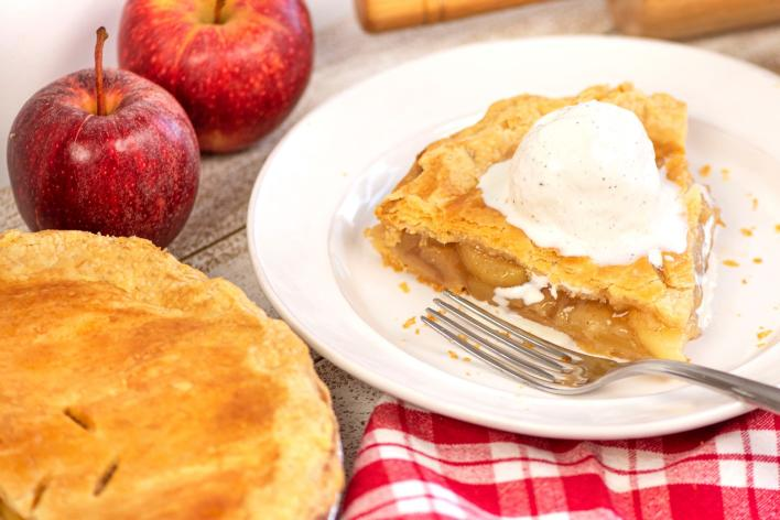 A slice of apple pie with ice cream on a plate near the entire pie on a table
