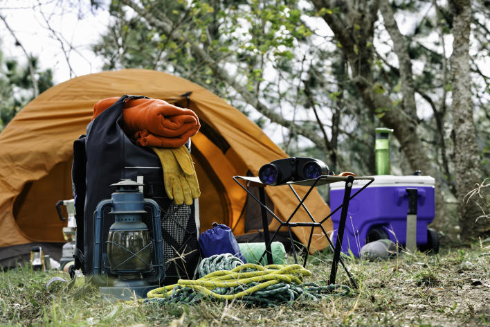 Camping gear in front of a tent in a forest