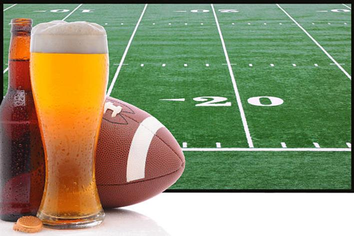 Bottle of beer, beer stein and football set in front of a football field